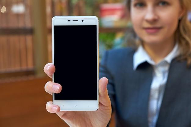 Kobieta biznesu z pustego ekranu inteligentnego telefonu. zamyka w górę tła miejsca dla teksta