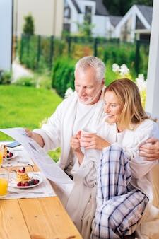 Kobieta blisko męża. atrakcyjna dojrzała kobieta w kraciastych spodniach od piżamy i białym szlafroku siedzi obok męża