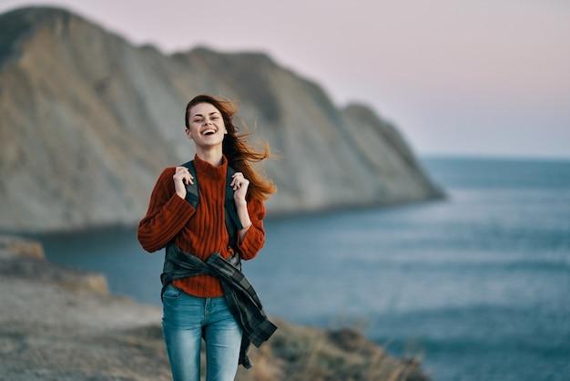 Kobieta blisko morza w przyrodzie i górach w tle turystyka model podróży