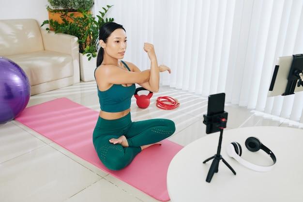 Kobieta blogerka fitness nagrywa wideo, jak rozprostować ramiona i rozgrzać się przed intensywnym treningiem w domu