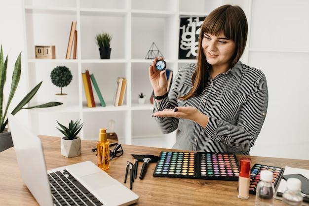 Kobieta blogerka makijażu z przesyłaniem strumieniowym z laptopa w domu