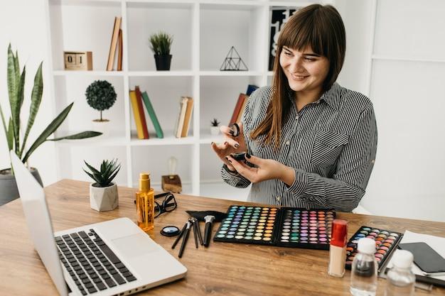 Kobieta blogerka makijażu z przesyłaniem strumieniowym z laptopa