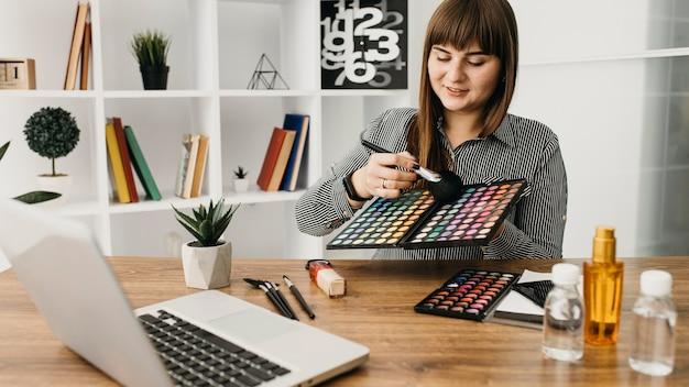 Kobieta blogerka makijażu ze streamingiem w domu z laptopem