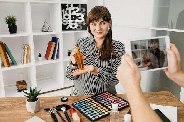 Kobieta blogerka makijażu ze streamingiem z tabletem w domu