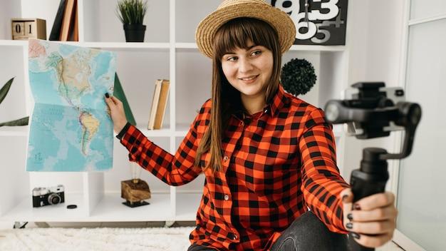 Kobieta blogerka podróżnicza w domu ze smartfonem i mapą
