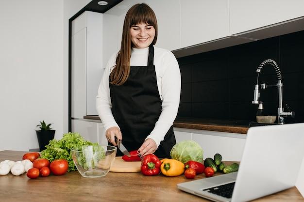 Kobieta blogerka przesyłania strumieniowego gotowania z laptopem
