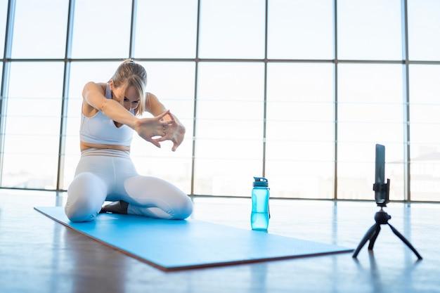 Kobieta blogerka sportowa nagrywa strumień fitness online