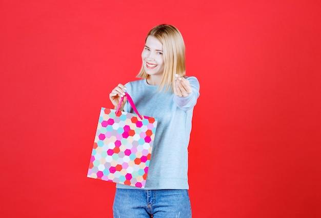 Kobieta blondynka robi znak pieniędzy, trzymając kolorową torbę przed czerwoną ścianą