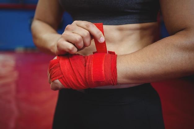 Kobieta bokser na sobie czerwony pasek na nadgarstku