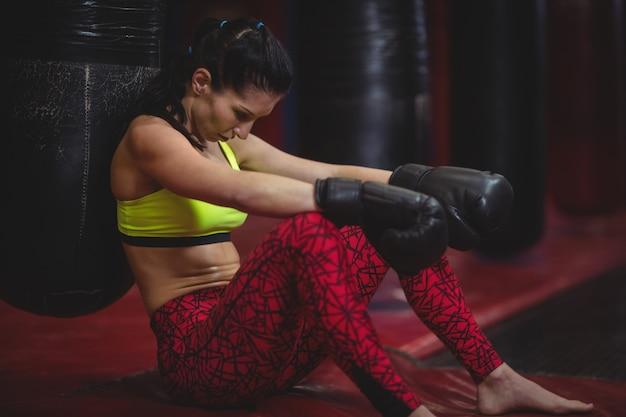 Kobieta bokser opierając się na worek treningowy