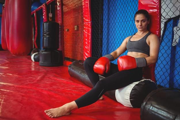 Kobieta bokser siedzi na worek treningowy
