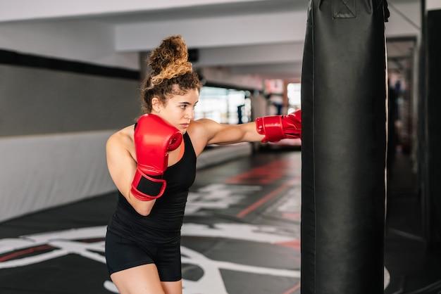 Kobieta bokser trenująca z czerwonymi rękawicami bokserskimi uderzającymi bezpośrednio w worek treningowy na siłowni