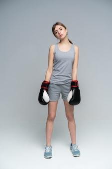Kobieta bokser z rękawic bokserskich stojących na szaro patrząc w dół