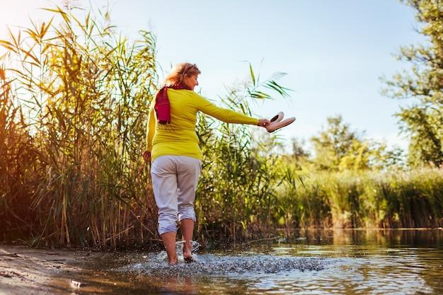 Kobieta boso w średnim wieku spaceru na brzegu rzeki w dzień wiosny. starsza pani zabawy w lesie z przyrodą.