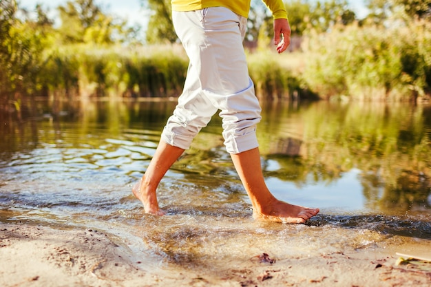 Kobieta boso w średnim wieku spaceru na brzegu rzeki w jesienny dzień. starsza pani zabawy w lesie z przyrodą. zbliżenie nóg