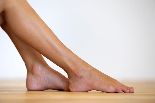 Kobieta bosymi stopami na podłodze. koncepcja pielęgnacji nóg i leczenia skóry.