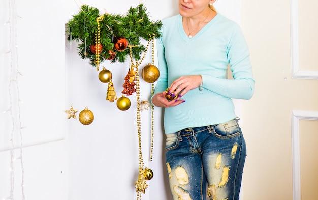 Kobieta, boże narodzenie lub nowy rok dekoracja przy żywym izbowym wnętrzem i wakacje wystroju domowym wystrojem.