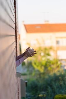 Kobieta brawa z domu, aby podziękować ludziom walczącym z koronawirusem