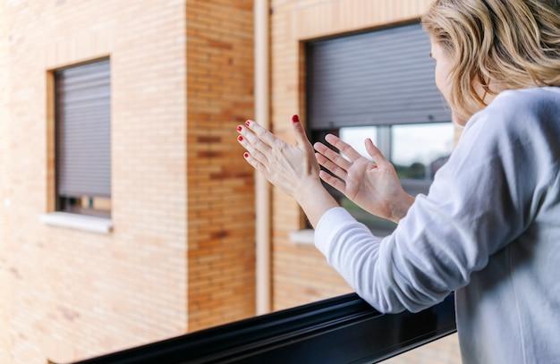 Kobieta brawo z balkonu, by wesprzeć walczących z koronawirusem