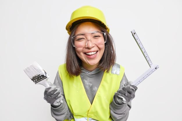 Kobieta budowlana będąca w dobrym nastroju trzyma pędzel i taśmę mierniczą szczęśliwa kończąc remont pokoju nosi odzież roboczą