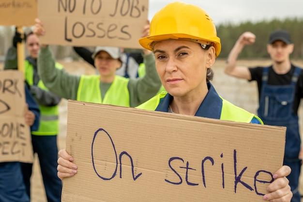Kobieta budowlana w średnim wieku trzymająca afisz podczas strajku