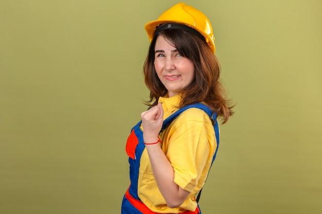 Kobieta budownicza ubrana w mundur budowlany i kask ochronny stojąca bokiem z pewnym uśmiechem podnoszącym pięść po koncepcji zwycięzcy zwycięstwa stojącej nad odizolowanymi zielonymi plecami