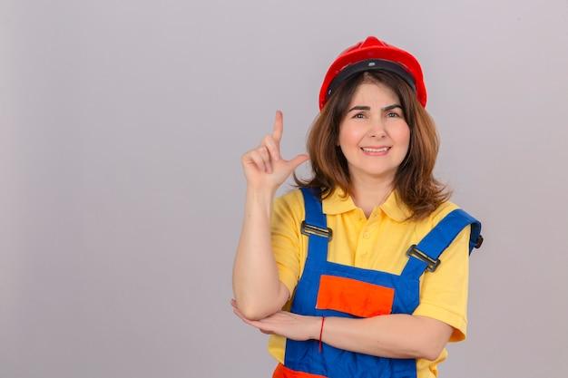 Kobieta budownicza w mundurze budowlanym i kasku ochronnym stojąca z uśmiechem na twarzy, wskazująca ręką i palcem w bok patrząc w kamerę nad izolowaną białą ścianą