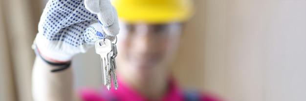 Kobieta budowniczy w kasku ochronnym trzymająca klucze w rękach zbliżenie