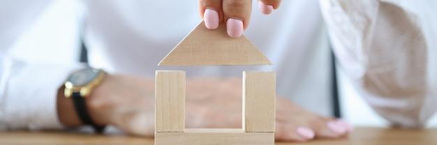 Kobieta buduje dom z drewnianych kostek na stole.