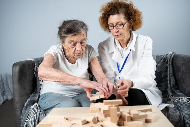 Kobieta buduje wieżę z drewnianych klocków z pomocą lekarza