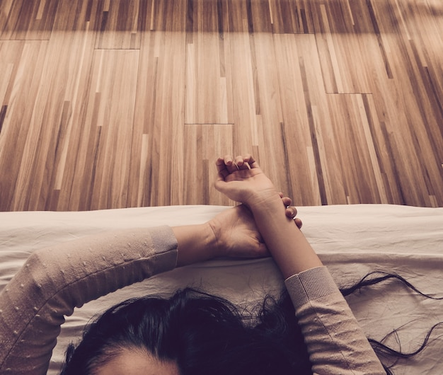 Kobieta budzi się i wyciąga ramiona o wschodzie słońca w łóżku z drewnianą podłogą