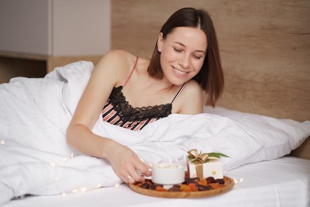 Kobieta budzi się na łóżku, a obok niej stoi prezent i kawa z piankami.
