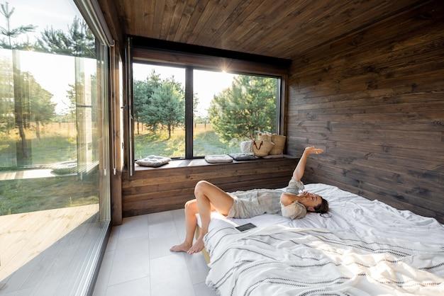 Kobieta budzi się w wiejskim domu lub hotelu z panoramicznymi oknami w sosnowym lesie leżąc na łóżku i unosi ręce ziewając. dzień dobry i rekreacja na koncepcji natury