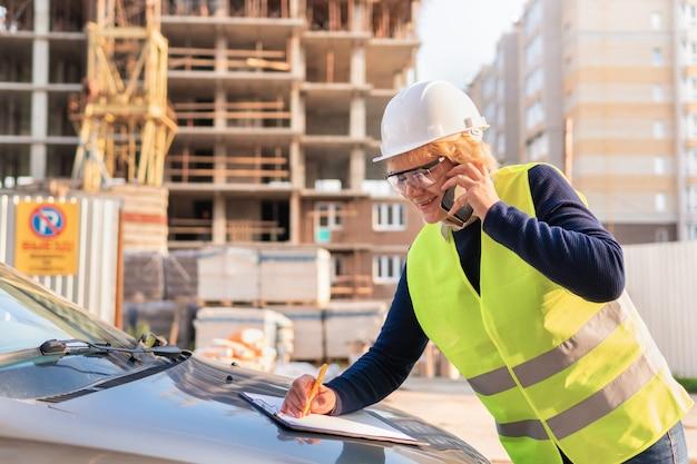 Kobieta builder z tabletem rejestruje wskaźniki. kobieta w średnim wieku pracująca na budowie. ma na sobie biały hełm i żółtą kamizelkę.