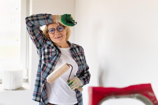 Kobieta builder z wałkiem do malowania. kobieta w średnim wieku robi naprawy w domu.