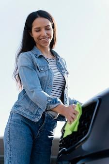 Kobieta buźka, czyszczenie jej samochodu na zewnątrz