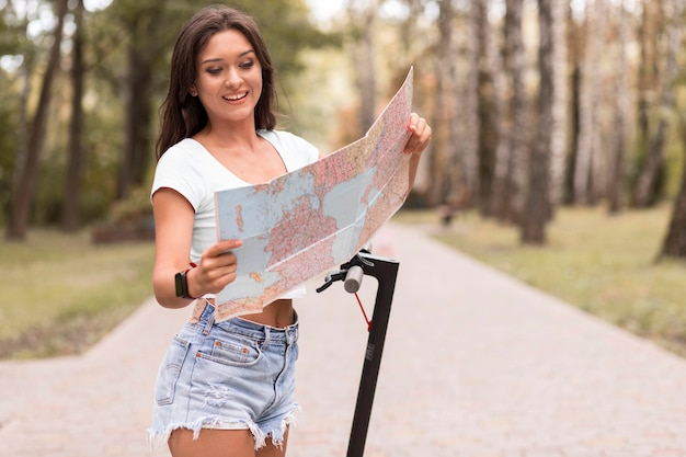 Kobieta buźka patrząc na mapę obok skutera elektrycznego