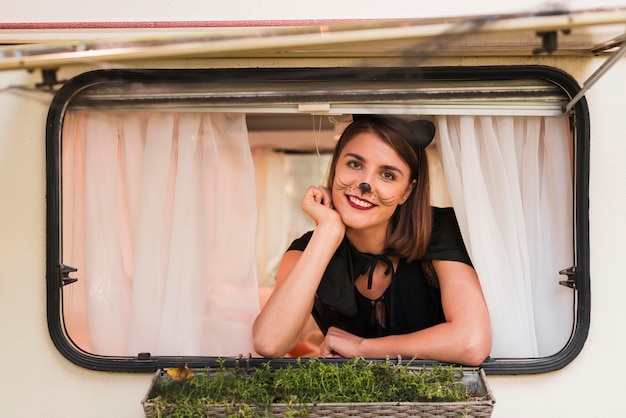 Kobieta buźka pozowanie na okno przyczepy kempingowej
