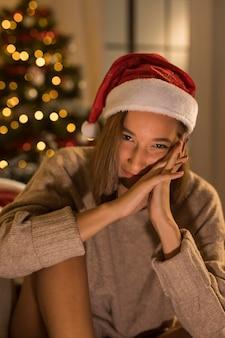 Kobieta buźka pozowanie podczas noszenia czapki santa