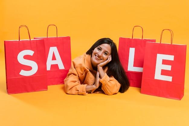 Kobieta buźka pozuje między torby na zakupy sprzedaży