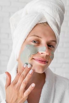 Kobieta buźka stosując środek zaradczy na twarz