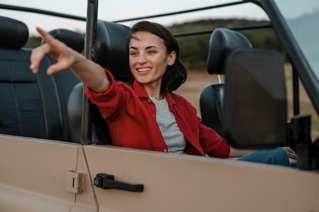 Kobieta buźka, wskazując podczas samotnej podróży samochodem