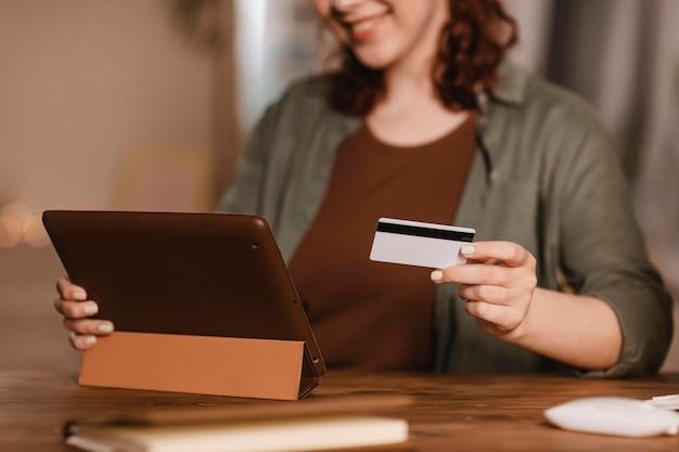 Kobieta buźka za pomocą tabletu w domu z kartą kredytową