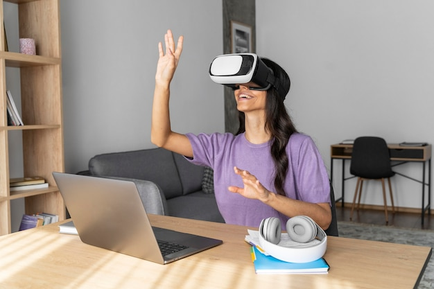 Kobieta buźka za pomocą zestawu słuchawkowego wirtualnej rzeczywistości w domu z laptopem