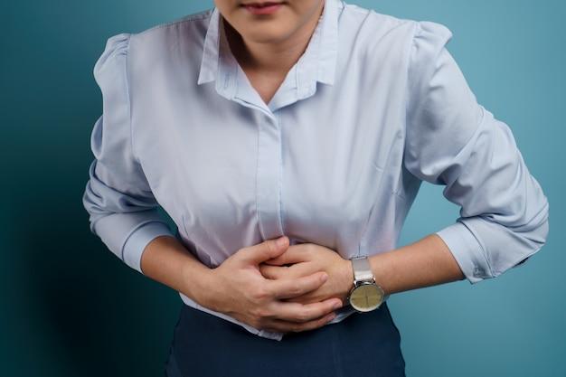 Kobieta była chora na ból brzucha trzymając się za ręce przyciskające jej brzuch.