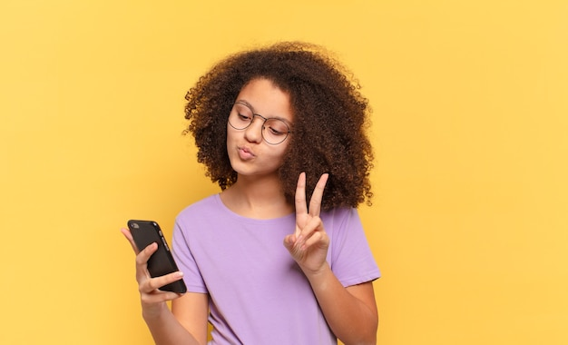 Kobieta całkiem afro nastolatek używając jej komórki