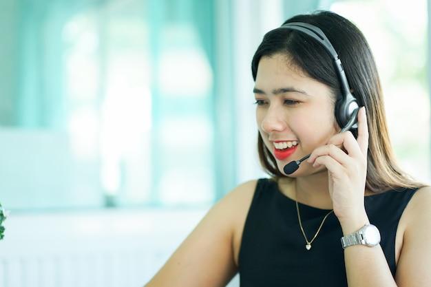 Kobieta call center pracuje rozmawiając przez słuchawki próbując odpowiedzieć na odpowiedź lub działając