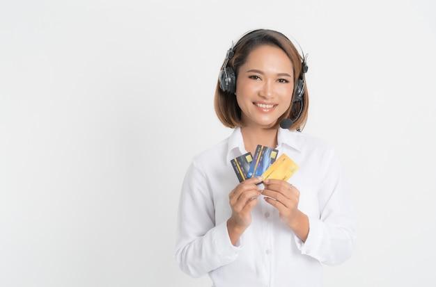 Kobieta call center z zestawu słuchawkowego gospodarstwa i karty kredytowej.