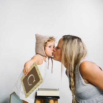 Kobieta całuje dziewczynę z listową kartą