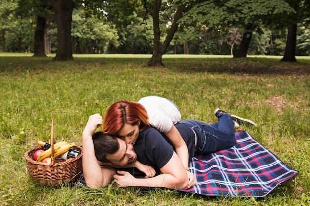 Kobieta całuje jej chłopaka lying on the beach na koc nad zieloną trawą w parku
